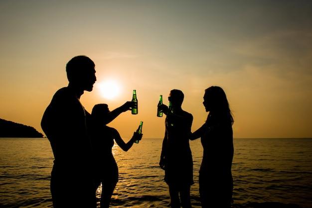 Groep jonge vrienden die en partij drinken hebben bij het strand in avondzonsondergang