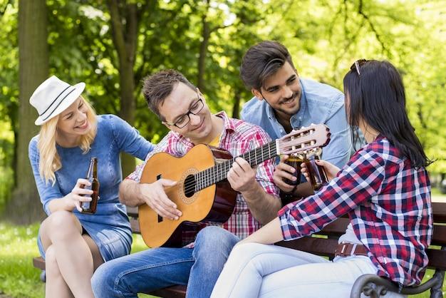 Groep jonge vrienden die gitaar spelen en bier drinken op een parkbank