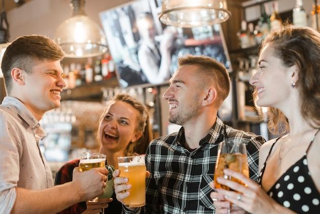 Groep jonge vrienden die in de bar genieten van