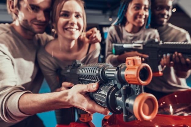 Groep jonge vrienden die met kanonnen in arcade stellen.