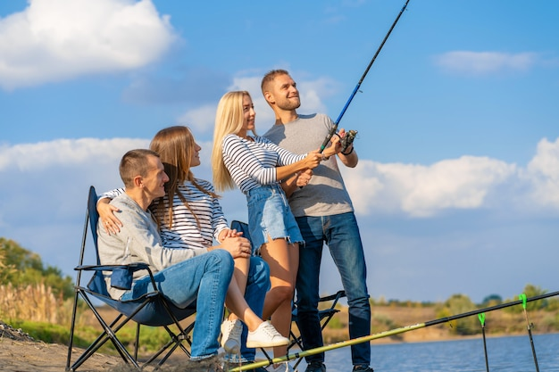 Groep jonge vrienden die op de pijler door oever van het meer vissen