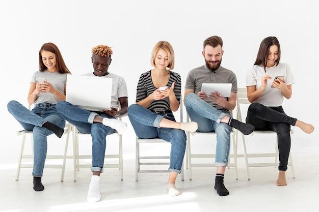 Groep jonge vrienden die op stoelen zitten
