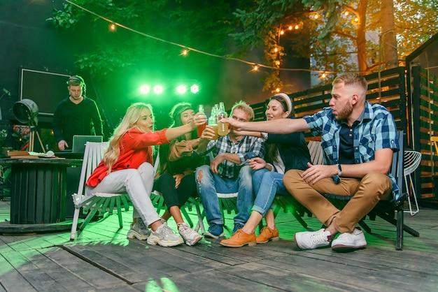 Groep jonge vrienden die plezier hebben op een zomerfeest bij het zwembad, bier drinken en meer vrienden uitnodigen om mee te doen