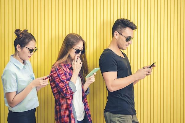 Groep jonge vrienden die slimme telefoon met behulp van tegen gele muur
