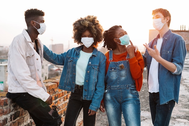 Groep jonge vrienden die uit met medische maskers hangen