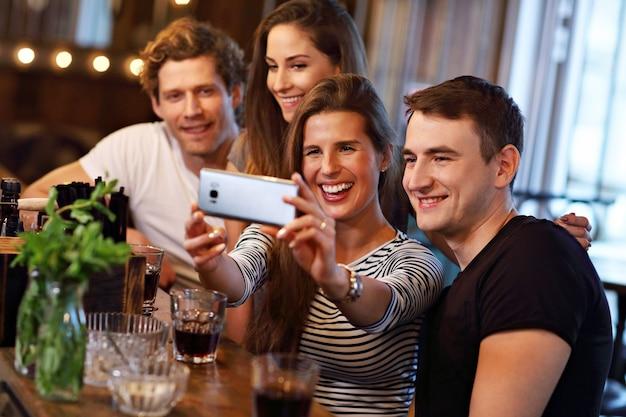 Groep jonge vrienden die van maaltijd in restaurant genieten