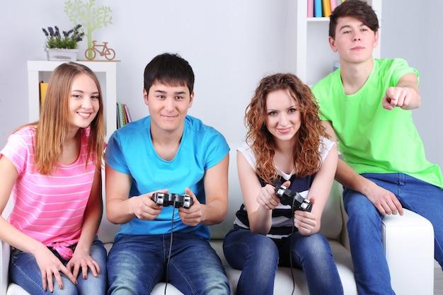 Groep jonge vrienden die videospelletjes thuis spelen