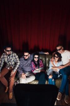 Groep jonge vrienden in 3d-bril hebben plezier en kijken samen naar tv-show op de bank, bovenaanzicht
