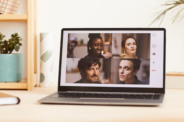 Groep jonge vrienden kijken naar camera vanaf de monitor van laptop hebben ze online conferentie