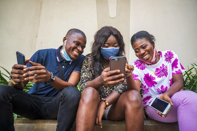 Groep jonge vrienden met beschermende gezichtsmaskers die hun telefoons buitenshuis gebruiken