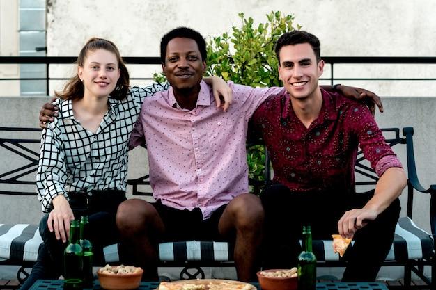 Groep jonge vrienden met pizza en flessen drank