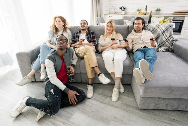 Groep jonge vrienden ontspannen op de bank in de woonkamer terwijl ze rode wijn hebben en thuis tv kijken