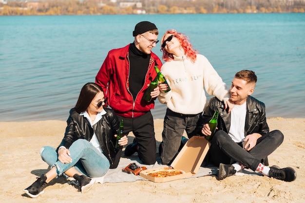 Groep jonge vrienden op picknick aan kust