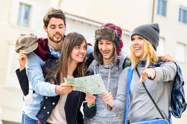 Groep jonge vrienden van hipstertoeristen die met stadskaart toejuichen in de oude stad