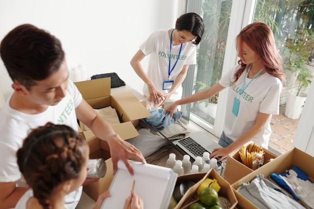 Groep jonge vrijwilligers die aan een grote tafel in het kantoor van het liefdadigheidscentrum staan en gegevens bijhouden van gedoneerde kleding, voedsel en water