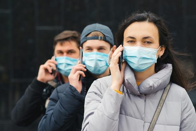 Groep jonge vrijwilligers die gezichtsmaskers met mobiele telefoons dragen. vrijwilligers staan klaar om te helpen.