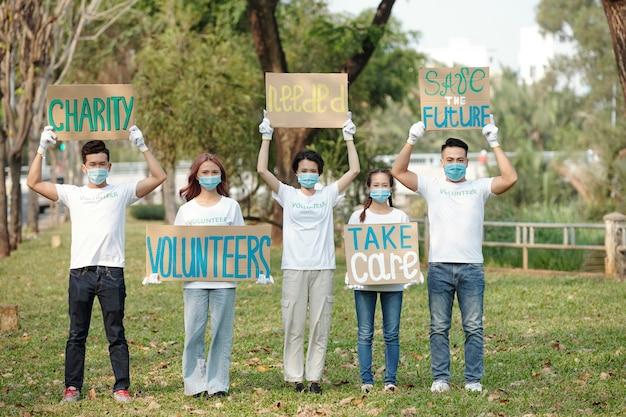 Groep jonge vrijwilligers die protesteren met verschillende borden in het stadspark