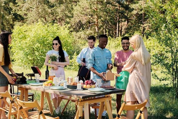 Groep jonge vrolijke internationale vrienden in vrijetijdskleding staan bij tafel onder dennenboom en zetten eten, drinken en bloemen erop
