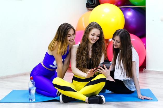 Groep jonge vrolijke kaukasische vrouwen die tabletpc in een geschiktheidsclub met behulp van.
