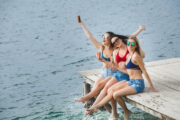 Groep jonge vrolijke meisjes die pret hebben bij het strand