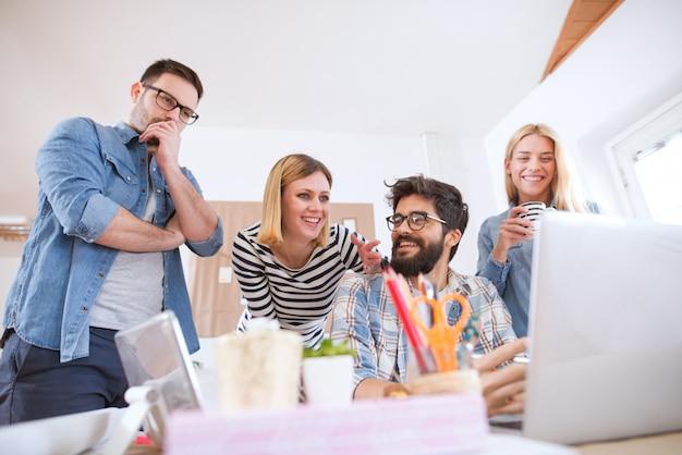Groep jonge vrolijke toegewijde business team bespreken verdere stappen terwijl een van hen zich zorgen maakt.
