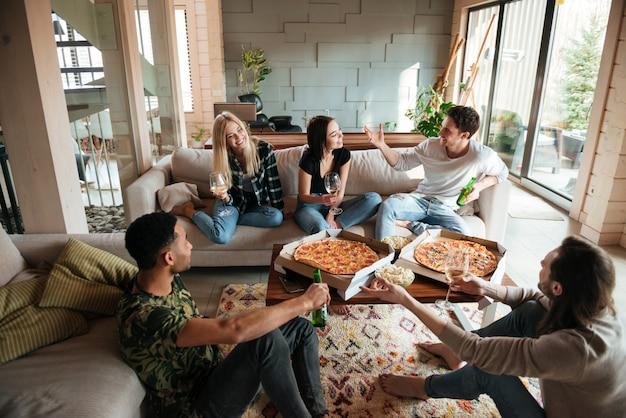 Groep jonge vrolijke vrienden die uit samen thuis hangen