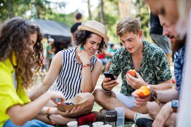 Groep jonge vrolijke vrienden op zomerfestival, zittend op de grond en eten.