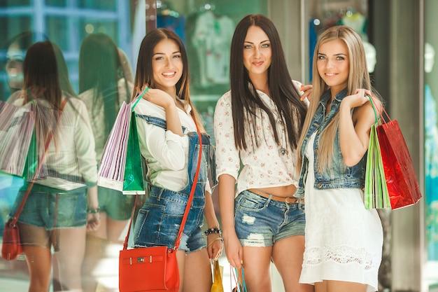 Groep jonge vrolijke vriendinnen winkelen