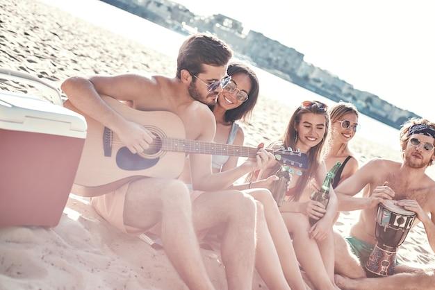Groep jonge vrouwelijke vrienden die op het strand op zonnebedden zitten, zingen en gitaarspelen bij zonsondergang