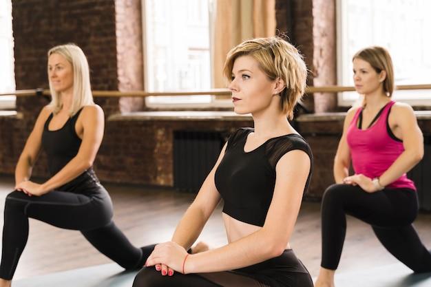 Groep jonge vrouwen die bij de gymnastiek uitwerken