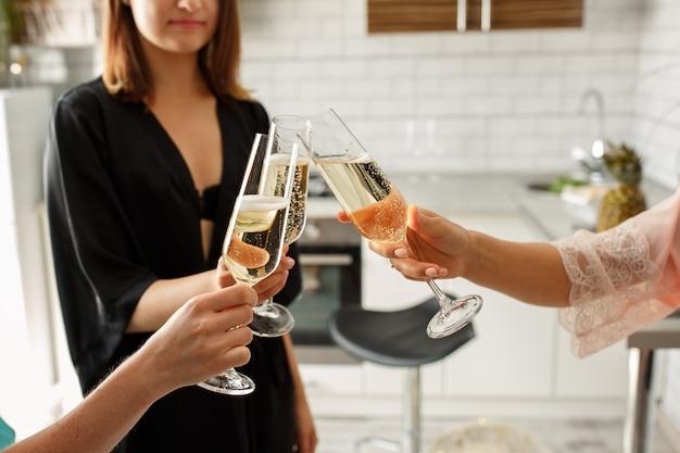 Groep jonge vrouwen die met champagne toejuichen, die vrijgezellenfeest thuis vieren
