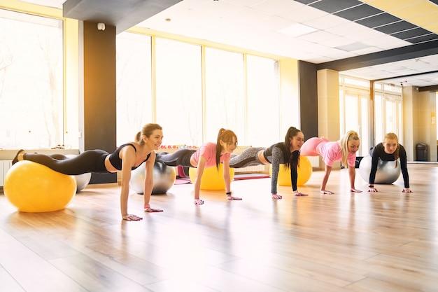 Groep jonge vrouwen die plank op medicijnbal samen in gymnastiek doen