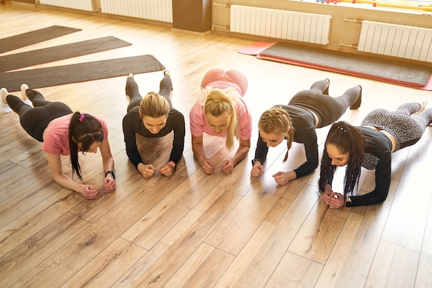 Groep jonge vrouwen die plank samen in gymnastiek doen