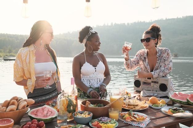 Groep jonge vrouwen die wijn drinken en voedsel bereiden voor het diner op de natuur buitenshuis