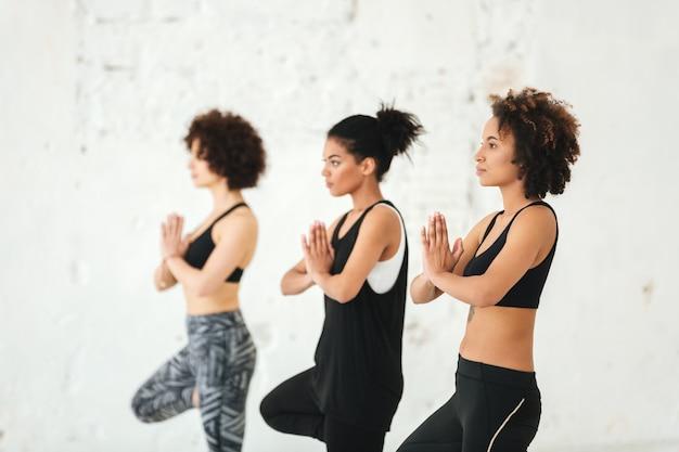 Groep jonge vrouwen die yogaoefeningen doen