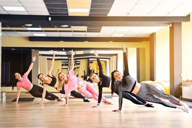 Groep jonge vrouwen die zijplank samen in gymnastiek doen