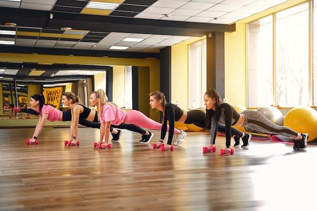 Groep jonge vrouwen doen plank op halters samen in de sportschool