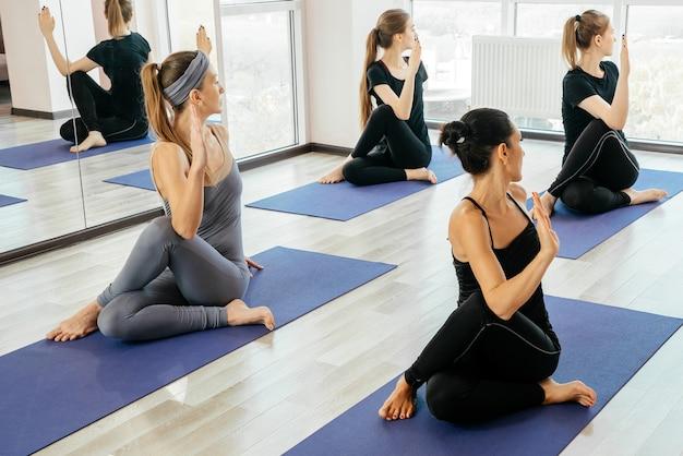 Groep jonge vrouwen doen yoga oefeningen in de studio, het maken van rekoefeningen in de klas binnenshuis