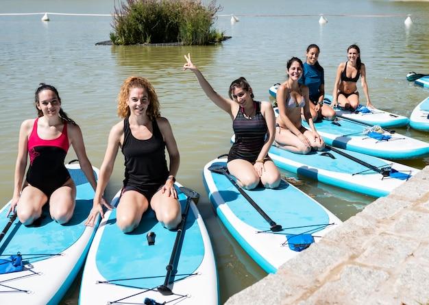 Groep jonge vrouwen in zwemkleding die in de vroege ochtend yoga op een stadsmeer doen. evenwichtige houding - concept van gezond leven en natuurlijk evenwicht tussen lichaam en geestelijke ontwikkeling.