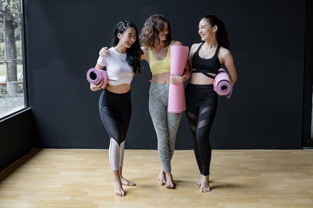 Groep jonge vrouwen met yogamatten die zich op zwarte muur in oefenruimte bevinden. vrouwelijke metgezellen in de sportschool rusten na yoga. concept van oefening met yoga.
