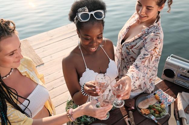 Groep jonge vrouwen roosteren met glazen witte wijn terwijl ze tijd doorbrengen op een pier buitenshuis