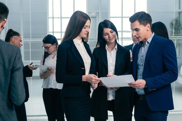 Groep jonge werknemers bespreken een bedrijfsdocument. kantoor werkdagen