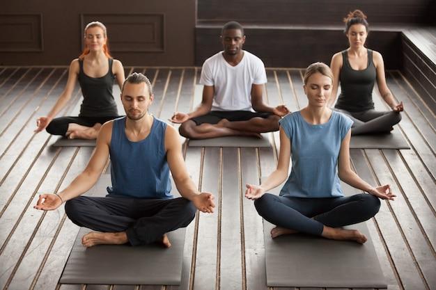 Groep jonge yogimensen die in oefening sukhasana zitten