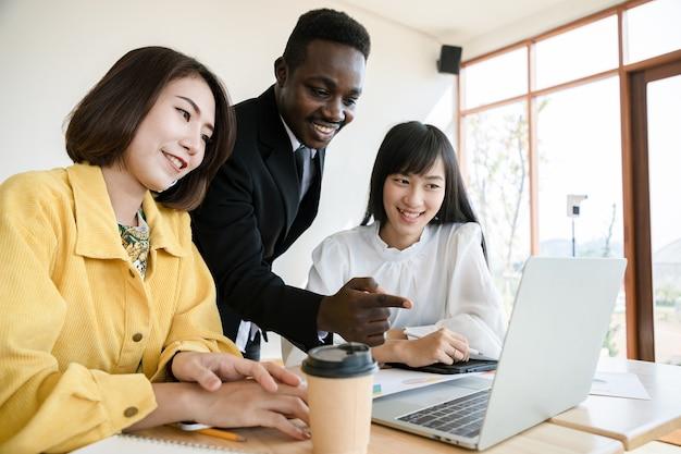 Groep jonge zakelijke bijeenkomst en maak afspraken over laptop in de organisatie. zakenmanleider op kantoor. succesvolle projecten en felicitatie.