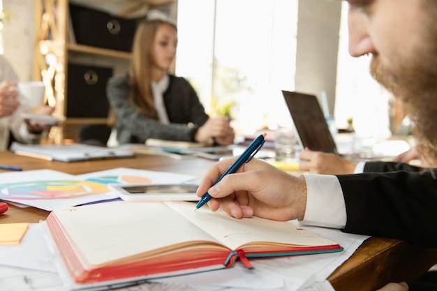 Groep jonge zakelijke professionals die een vergadering hebben. diverse groep collega's bespreken nieuwe beslissingen, plannen, strategie. creatieve werkplek, business, financiën, teamwork. sluit omhoog van het schrijven van de mens.