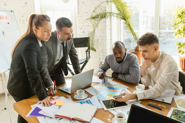 Groep jonge zakelijke professionals die een vergadering hebben. diverse groep collega's bespreken nieuwe beslissingen, toekomstplannen en strategie. creatieve vergadering en werkplek, zaken, financiën, teamwork.