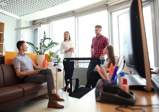 Groep jonge zakelijke professionals die een vergadering hebben. diverse groep jonge ontwerpers die glimlachen tijdens een vergadering op kantoor.