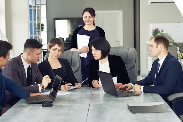 Groep jonge zakenmensen die op kantoor samenkomen om samen een belangrijk idee te bespreken