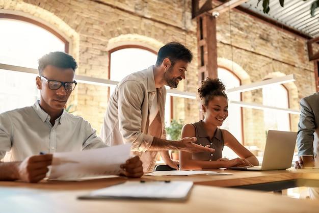 Groep jonge zakenmensen die samenwerken en met elkaar communiceren