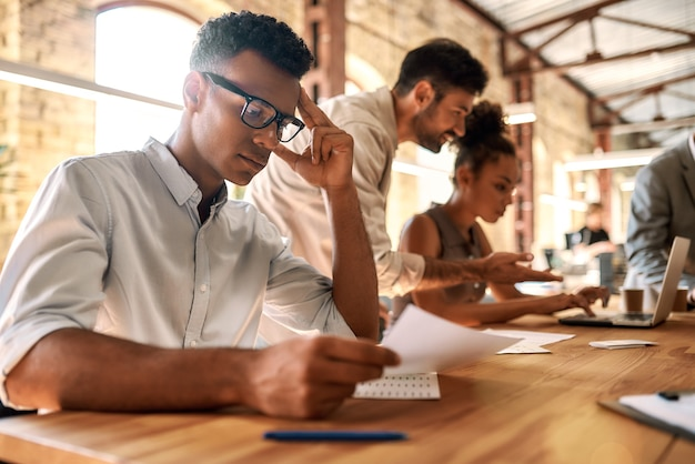 Groep jonge zakenmensen die samenwerken terwijl ze aan de kantoortafel zitten